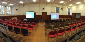 hall set up in theatre style with 2 screens