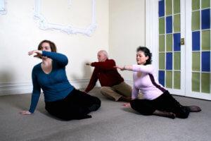 awareness through movement class, 3 people doing yoga